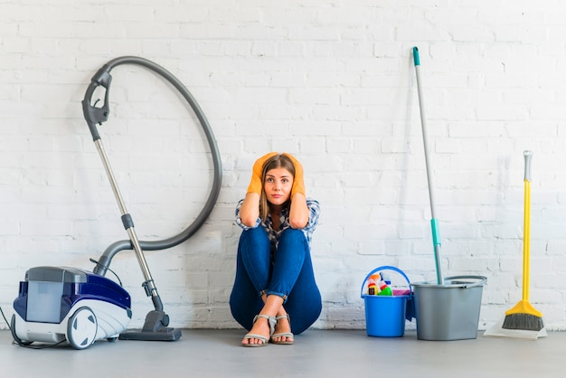 Preocupado, empregada doméstica, femininas, sentando, perto, limpeza, equipamentos, frente, parede tijolo Foto gratuita
