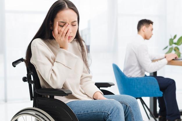 Preocupado, mulher jovem, sentando, ligado, cadeira roda, sentando, frente, macho, colega, usando computador portátil Foto gratuita