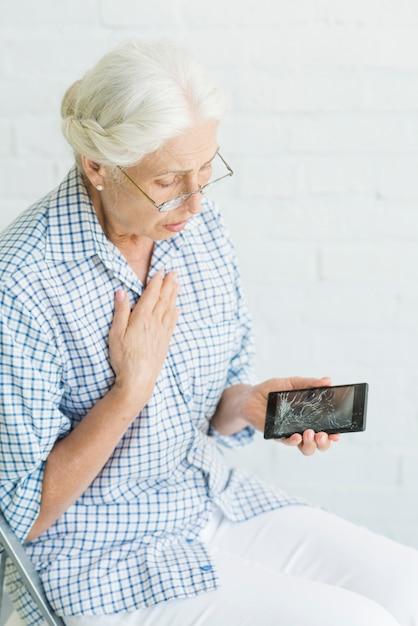 Preocupado mulher sênior olhando para smartphone com tela quebrada contra parede branca Foto gratuita