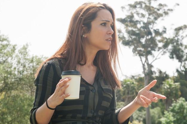 Preocupado senhora tomando café no parque Foto gratuita
