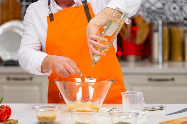 Preparação da cozinha: o chef mistura os ingredientes na tigela Foto Premium