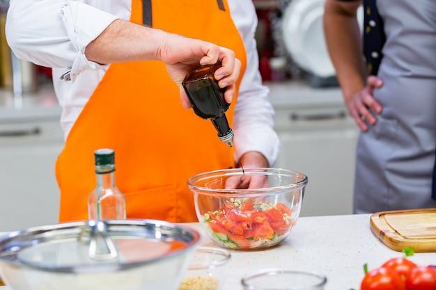 Preparação da cozinha: o chef prepara uma salada Foto Premium