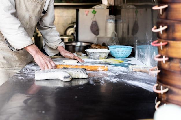 Preparação de massa de pão padaria, mãos de padeiros, farinha é derramada, fazendo sobremesa local de sichuan Foto Premium