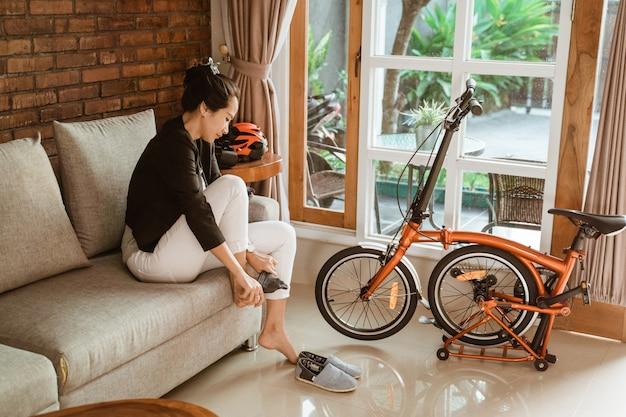 Preparação do trabalhador de mulher asiática, sentado no sofá usando meias Foto Premium