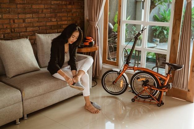 Preparação do trabalhador de mulher asiática, sentado no sofá usando sapatos Foto Premium