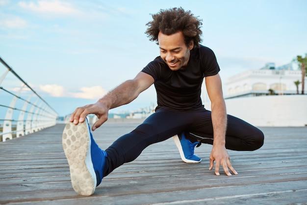 Preparação física e motivação. atleta de pele escura alegre e sorridente, alongando-se no cais pela manhã. afro-americano desportivo com cabelo espesso aquecendo as pernas Foto gratuita