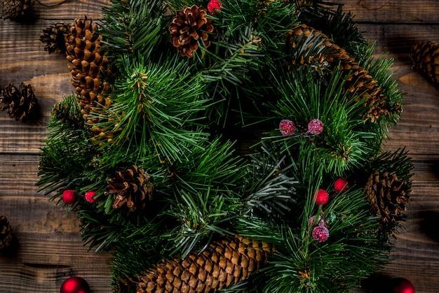 Preparação para as férias de natal. guirlanda verde decorativa de natal com pinhas e bagas vermelhas de inverno e bolas de árvore de natal Foto Premium