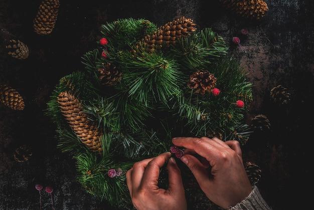 Preparação para as férias de natal. mulher que decora a grinalda verde do natal com pinhas e bagas vermelhas do inverno, no escuro enferrujado, vista superior copyspace, mãos femininas Foto Premium