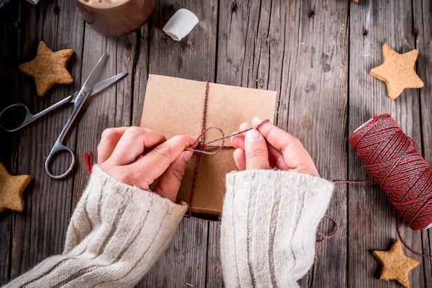Preparação para as férias de outono e inverno. a pessoa embala os biscoitos como um presente em uma caixa de artesanato, fita de natal, mãos no quadro. mesa antiga rústica, espaço de cópia de vista superior Foto Premium