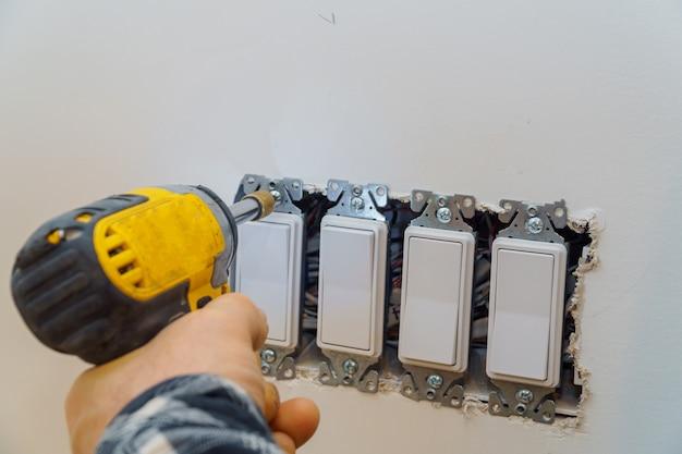 Preparando-se para instalar uma tomada elétrica, verificando a fixação dos parafusos Foto Premium