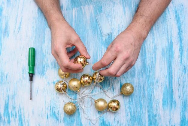Preparando-se para o ano novo. reparo de uma guirlanda elétrica de abeto. nas mãos de um eletricista, clippers e pinça Foto Premium
