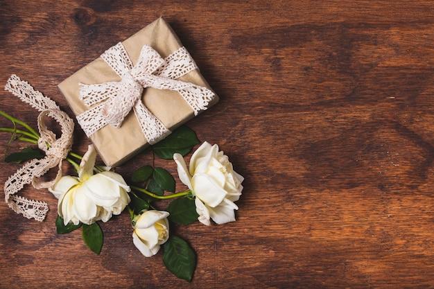 Presente amarrado com guardanapo e buquê de rosas Foto gratuita