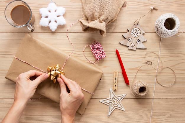 Presente com decorações de natal em fundo de madeira Foto gratuita
