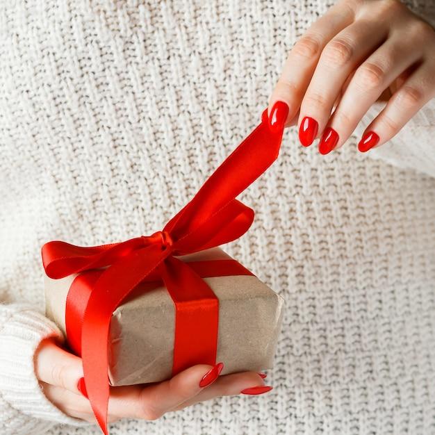 Presente com uma fita vermelha nas mãos sobre um fundo branco Foto Premium