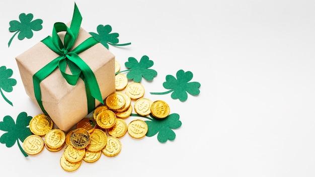 Presente de alto ângulo, moedas e trevos Foto gratuita