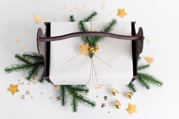 Presente de ano novo de luxo com decoração de ouro e galhos de árvores. presente de natal em cesta de madeira. fundo de natal com caixa de presente. presentes para a celebração de natal. Foto Premium