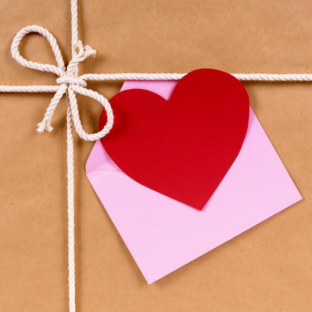 Presente de dia dos namorados com cartão de forma de coração ou etiqueta de presente, pacote de papel pardo Foto gratuita