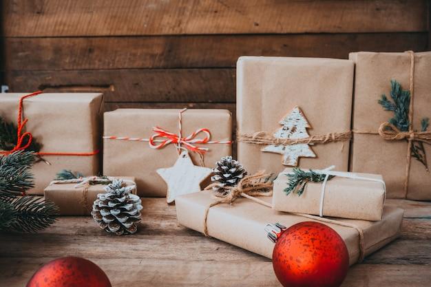 Presente de natal artesanal com tag para feliz natal e ano novo. caixas de presente de artesanato rústico. tom de cor vintage. Foto Premium