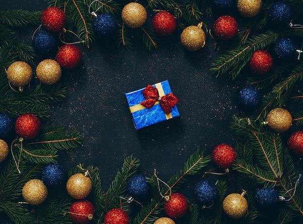 Presente de natal em um fundo preto com abeto e vista superior Foto Premium