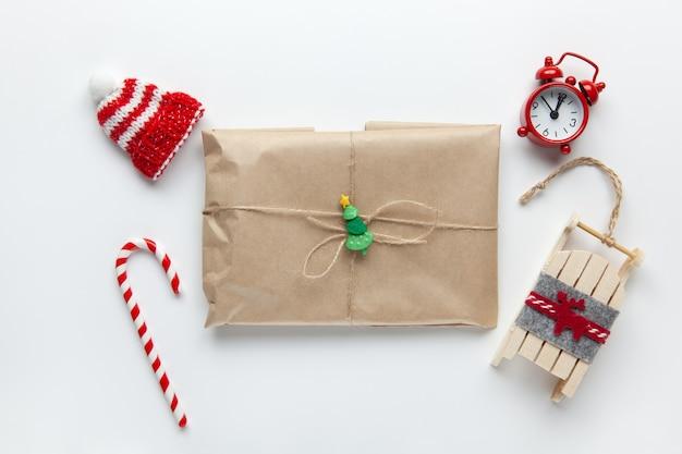 Presente de natal embrulhado em papel ofício marrom, amarrado com açoite, com doce de cana, pequeno relógio analógico, trenó, chapéu branco Foto Premium