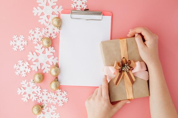 Presente de natal nas mãos das mulheres e notebook em um rosa, uma vista de cima Foto Premium
