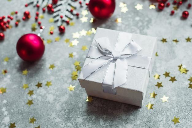 Presente de prata com laço cinza com bolas vermelhas de natal e confetes dourados Foto Premium
