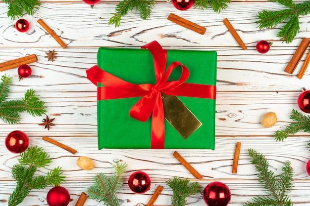 Presente embrulhado em um fundo de madeira com vista superior de decorações de férias de natal Foto Premium