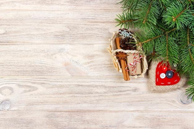 Presente festivo boxe com coração, estrela anice, cesta, canela e floco de neve em fundo de madeira. presentes de natal com copyspace Foto Premium