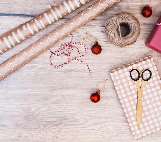 Presente no envoltório perto de bolas de natal, torções e tesouras Foto gratuita