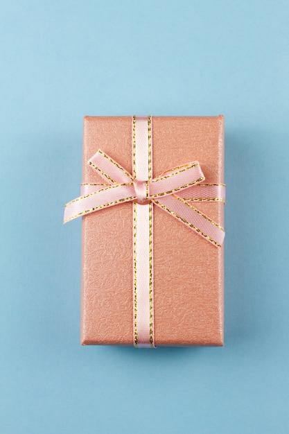 Presente pequeno em um fundo pastel, close up. caixa de presente com um laço Foto Premium