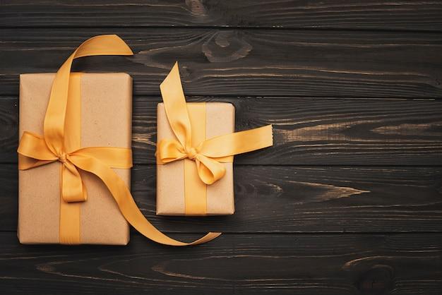 Presentes amarrados com fita dourada sobre fundo de madeira e cópia espaço Foto gratuita