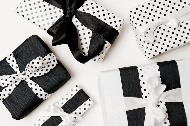 Presentes de aniversário apresenta caixa embrulhada com papel de bolinhas brancas e pretas lindas Foto gratuita