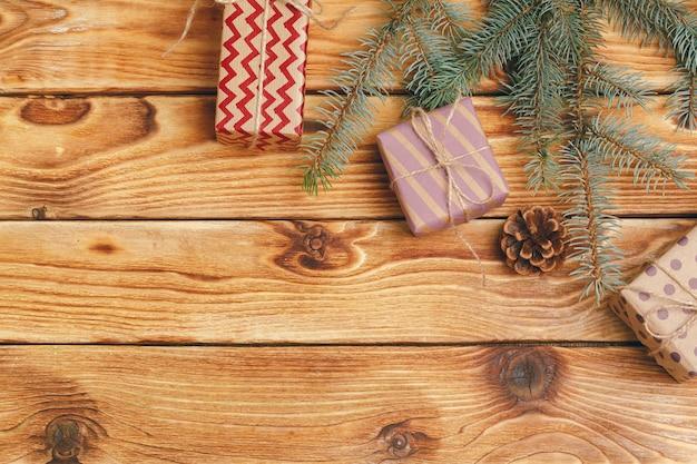 Presentes de natal com galhos de árvore do abeto em fundo de madeira Foto Premium