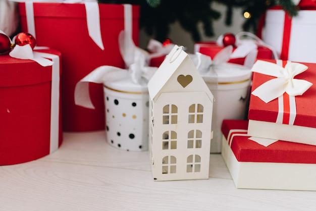 Presentes de natal e objetos em vermelho e branco debaixo da árvore de natal Foto Premium