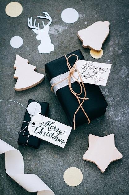 Presentes de natal em embalagem preta com etiquetas, confetes e decoração em madeira sobre um fundo cinza Foto Premium