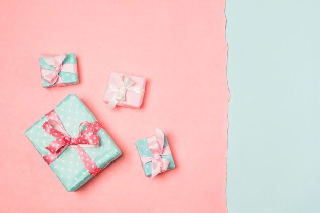 Presentes decorados com fitas dispostas em superfície dupla cor Foto gratuita