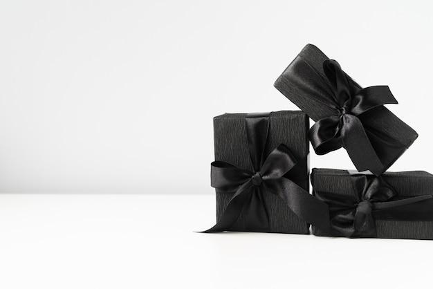 Presentes embrulhados preto sobre fundo liso Foto gratuita