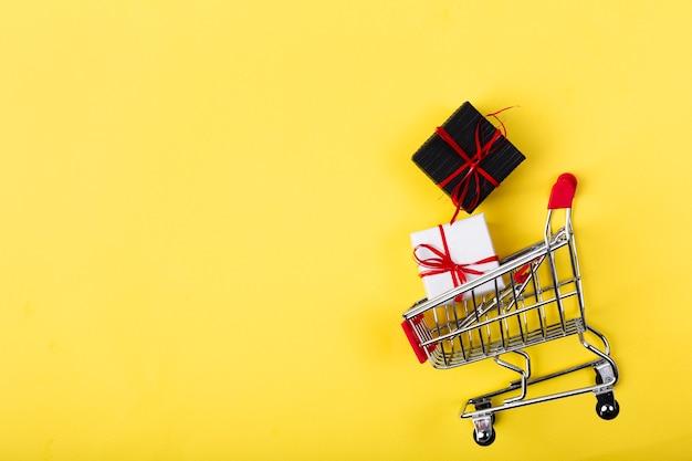 Presentes pretos de sexta-feira dentro do carrinho de compras Foto gratuita