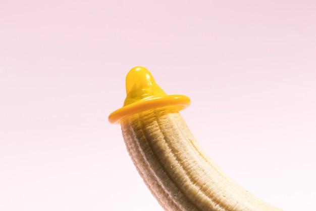 Preservativo desembrulhado amarelo em uma banana Foto gratuita
