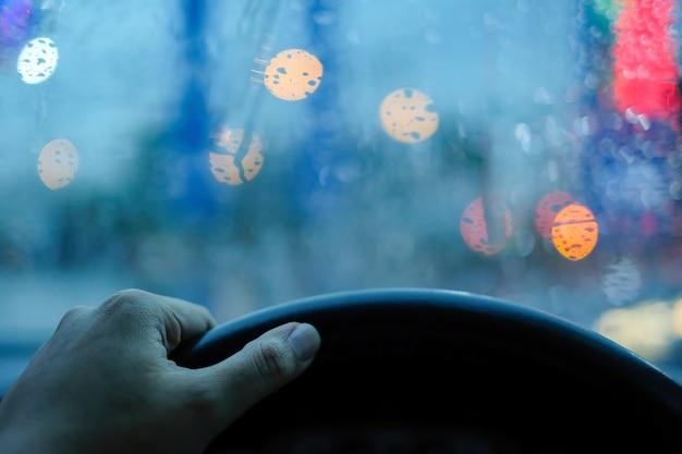 Preso na mão do carro agarrar volante e gotas de chuva no pára-brisa com boke embaçada Foto Premium