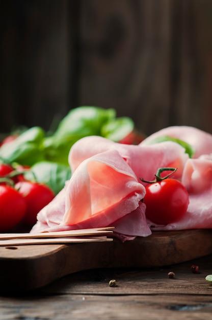 Presunto tradicional italiano com tomate e manjericão na mesa de madeira Foto Premium