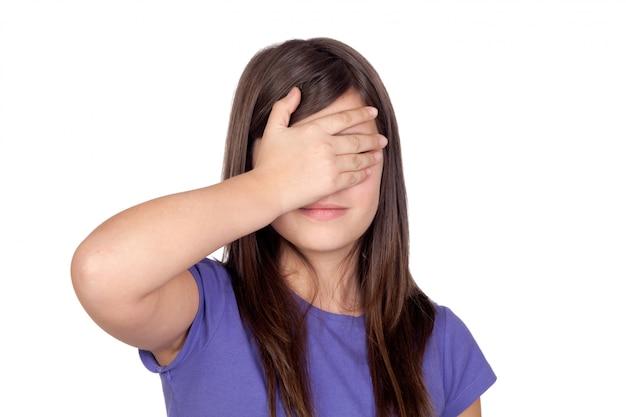 Preteen adorável que cobre seus olhos em um fundo branco Foto Premium