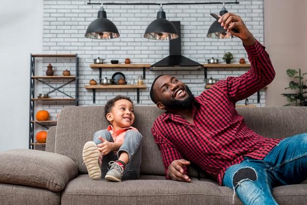Preto feliz pai e filho tomando selfie Foto gratuita