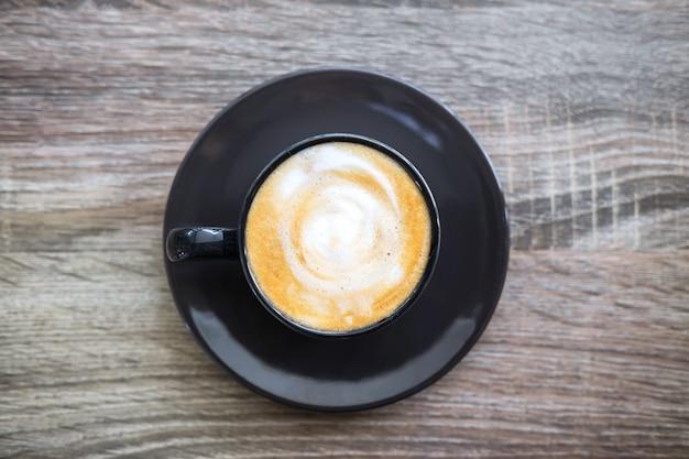 Preto xícara de café com espuma de leite tão deliciosa na velha mesa de madeira Foto Premium