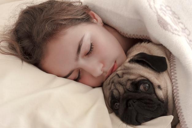 Pretty girl teen dorme abraçando um cão pug na cama Foto Premium
