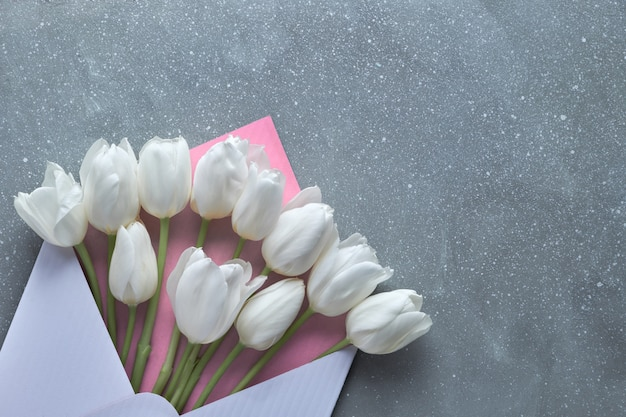Primavera plana leigos, tulipas brancas em envelope branco e rosa Foto Premium