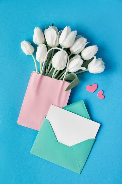 Primavera plana leigos, tulipas brancas em saco de papel em fundo azul menta com envelope, cartão em branco e corações decorativas Foto Premium