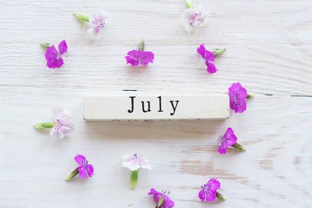 Primeiro dia de julho, fundo colorido com calendário e flores cor de rosa Foto Premium