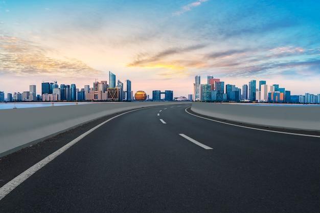 Primeiro plano, rodovia, asfalto, pavimento, cidade, predios, comercial, predios, edifício escritório Foto Premium
