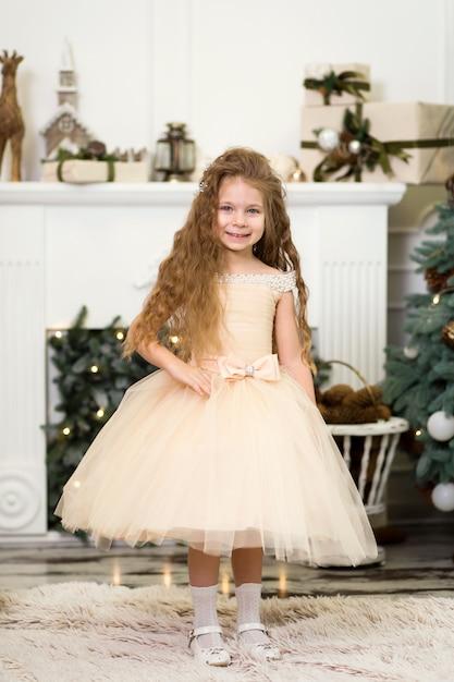 Princesa menina bonitinha em um vestido chique ri e posa perto da árvore de natal Foto Premium